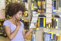Instrucciones afroamericanas de la lectura de la mujer en un producto en el mercado estupendo foto de archivo libre de regalías