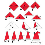Instrucciones paso a paso cómo hacer el casquillo de Papá Noel de la papiroflexia Foto de archivo
