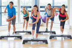Instructeur avec la classe de forme physique exécutant l'exercice d'aérobic d'étape avec des haltères Image libre de droits