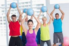 Instructeur avec la classe s'exerçant avec des boules de forme physique Image stock