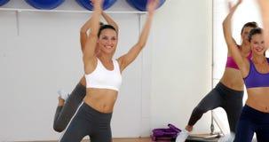 Instructeur d'aérobic menant une classe heureuse des femmes Photographie stock