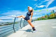 Instructeur de forme physique de femme faisant la ville extérieure s'exerçante de jour d'été Image stock