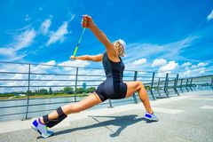 Instructeur de forme physique de femme faisant la ville extérieure s'exerçante de jour d'été Image libre de droits