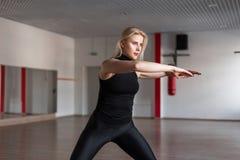 Instructeur de forme physique de jeune femme dans des expositions élégantes noires de vêtements comment maintenir l'équilibre se  photos libres de droits