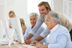 Instructeur de sourire avec des aînés dans la formation de classe Image libre de droits