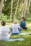Instructeur de yoga avec des aînés dehors Image stock