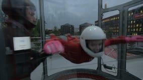 Instructeur die het jonge vrouw skydiving onderwijzen Uiterste die in windtunnel parachuteren stock videobeelden