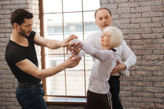 Instructeur doué de danse enseignant les couples vieillissants à la salle de bal Photographie stock libre de droits