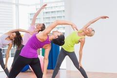 Instructeur et amis féminins faisant étirant l'exercice Photo stock