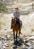 Instructeur of koeienhoeder het berijden paard in zonnebril, cowboyhoed en ruiterlaarzen Stock Foto's