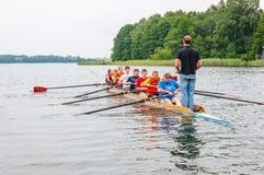 Instructeursbus onderwijzen toeristen hoe de het roeien acht boot in de wateren van Galve meer werkt Acht zijn een het roeien bin royalty-vrije stock foto's