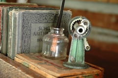 Instruction. Objects on a teacher's desk in a one-room schoolhouse, including tattered books, an old pencil sharpener, and an ink well stock photography