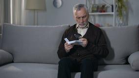 Instruction de lecture de vieil homme pour des pilules avec la loupe, traitant l'affaiblissement de vision clips vidéos