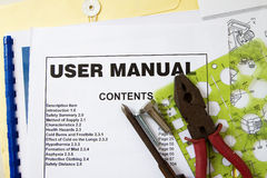 Instruction Manual. User manual guide brochure against tools and documents stock photo