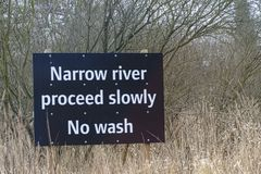 Instruction sign for boats, Narrow River proceed slowly. No wash stock photography