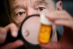 Instructions de examen d'homme sur la bouteille de médecine images stock
