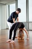 Instructor Adjusting Woman's Yoga Posture Royalty Free Stock Photo