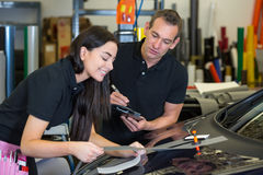 Instructor and apprentice in car wrapping workshop. Worker instructing female apprentice in car wrapping workshop royalty free stock images