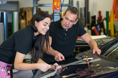 Instructor and apprentice in car wrapping workshop Royalty Free Stock Image