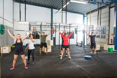 Instructor Assisting Athletes In Lifting Barbells Royalty Free Stock Photo