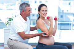 Instructor assisting cheerful pregnant woman Stock Photo