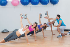 Instructor assisting fitness class with kettlebells Royalty Free Stock Photo
