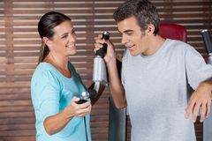 Instructor Assisting Man In Getting Down From. Mature female instructor assisting men in getting down from exercise machine in health club Royalty Free Stock Photo