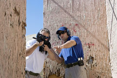 Instructor Assisting Man With Machine Gun Stock Photography