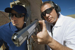 Instructor Assisting Officer With Hand Gun Stock Photos