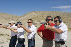 Instructor Assisting Officers At Firing Range. Instructor assisting officers with handguns at firing range during combat training Royalty Free Stock Image