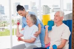 Instructor assisting senior woman in lifting dumbbells by man. Young female instructor assisting senior women in lifting dumbbells by men at gym Stock Photo
