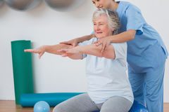 Instructor assisting senior woman to exercise Royalty Free Stock Image