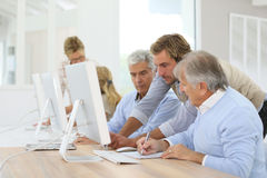 Instructor assisting seniors in class. Instructor helping senior men with computing class Stock Image