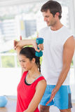 Instructor assisting woman with dumbbell weight Royalty Free Stock Photo