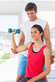 Instructor assisting woman with dumbbell weight Stock Images