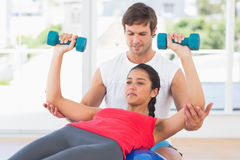 Instructor assisting woman with dumbbell weights Stock Images
