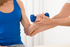 Instructor Assisting Woman For Exercising With Dumbbell stock photos