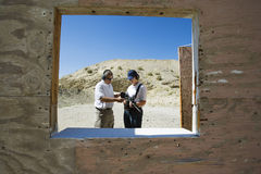 Instructor Assisting Woman At Firing Range In Desert Royalty Free Stock Images