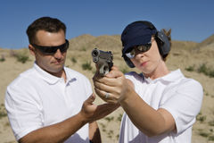 Instructor Assisting Woman With Hand Gun Stock Photo
