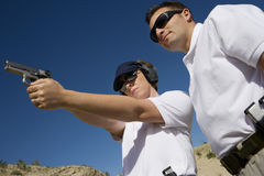 Instructor Assisting Woman With Hand Gun At Firing Range. Low angle view of instructor assisting women with hand gun at firing range Royalty Free Stock Photo
