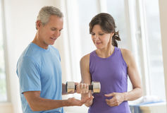 Instructor Assisting Woman In Lifting Dumbbell. Mature male instructor assisting women in lifting dumbbell at gym Royalty Free Stock Image