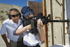 Instructor Assisting Woman With Machine Gun Stock Image