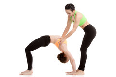 Instructor assists student in urdhva dhanurasana yoga Pose Royalty Free Stock Photography