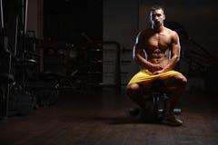 Instructor cansado después de entrenar con los pesos del gimnasio imagenes de archivo