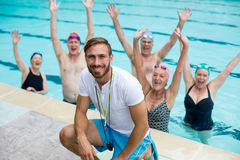 Instructor with carefree senior swimmers in pool. Portrait of male instructor with carefree senior swimmers in pool Stock Photo