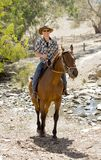 Instructor or cattleman riding horse in sunglasses, cowboy hat and rider boots. Young horse instructor or cattleman riding the animal wearing sunglasses, cowboy royalty free stock photos