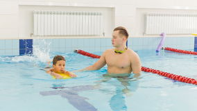 Instructor and child doing exercises in swimming pool. Coach teaches boy to swim stock video