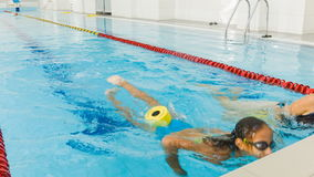 Instructor and child doing exercises in swimming pool. Coach teaches girl to swim stock video footage