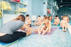 Instructor with children doing exercises. Woman instructor with children doing stretching exercises near swimming pool. Healthy and happy childhood concept Stock Photo