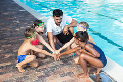 Instructor and children stacking hands at poolside. High angle view of instructor and children stacking hands at poolside Stock Photo